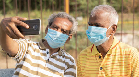 elderly friends with medical face mask taking selfie while sitting at park