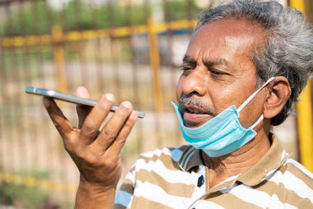 Senior man with medical face mask below the jaw talking on mobile phone at park -