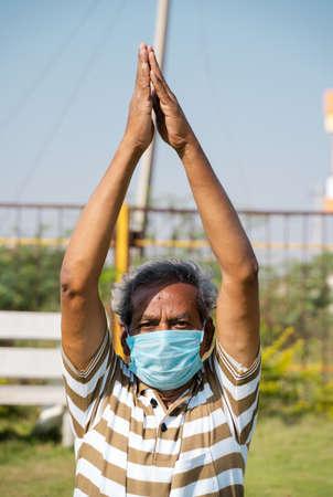 Old man with medical face mask busy doing surya namaskara yoga or exercise during morning