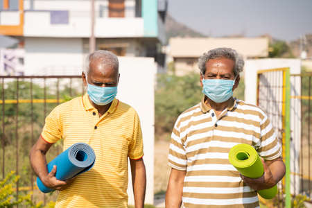 Two Senior people with yoga mat and medical face mask in park - Healthy elderly men with fitness mat coming