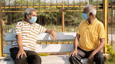 Two old senior friends with medical mask spending good time by talking and while maintaining social distancing at park id-19 pandemic 免版税图像