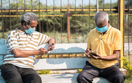 Two elderly people with medical face mask busy using mobile phone while sitting at park while maintaining social distance - concept seniors using smartphone, technology, social media and apps. 免版税图像