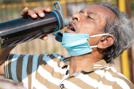 old man drinking water from bottle by placing mask below face during hot sunny day