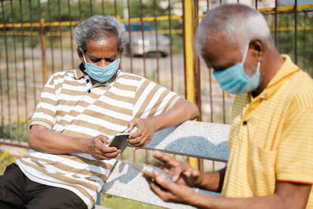 Sideview of Two senior men with medical face mask using mobile phone while sitting at park by maintaining social distance concept of  pandemic new normal and safety measures 免版税图像