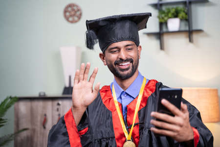 Student attending his online video graduation celebration from mobile phone in graduation dress - concept of virtual celebrations