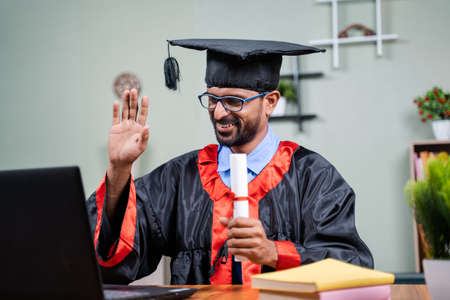 Student attending virtual graduation from laptop by holding certificate in graduation dress from home - concept of virtual celebrations