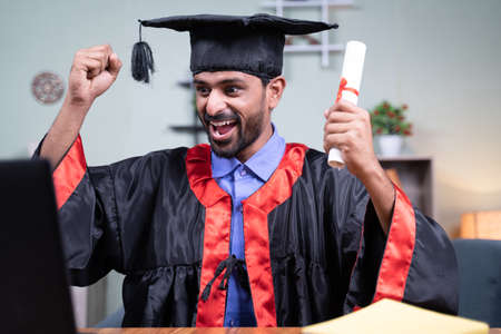 Young man excited over announcing graduation names over video call while holding certificate - concept virtual graduation new normal