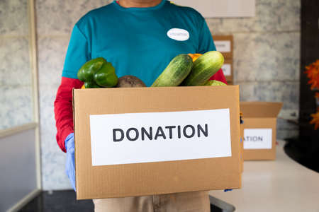 unrecognizable volunteer holding donation box with vegetables - Concept of people volunteering to help others during coronavirus covid-19 pandemic lockdown.