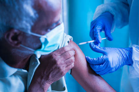 Senior elderly patient with mask getting vaccination or jab at hospital - Doctor in protective Hazmat suit treating Covid patient injecting anti-viral vials at covid care Centre