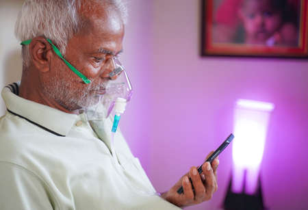 Old man with Oxygen concentrator mask reading news using mobile phone during home isolation - Concept of low oxygen level or therapy treatment from home for covid-19 coronavirus infected people