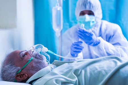 Focus on patient, doctor with protective suit preparing injection syringe while patient breathing on ventilator oxygen mask due to coronavirus covid-19 viral infection at hospital. Stock fotó