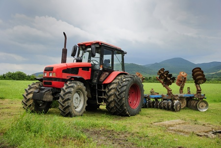 Red tractor parked on a grass field  photo