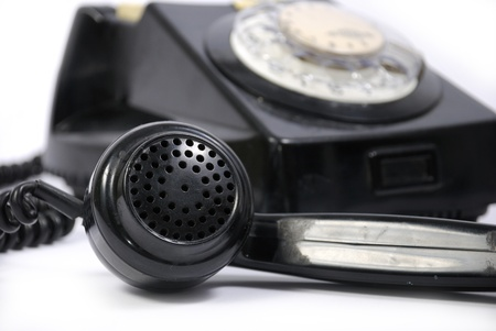 Old black phone with focus on the handset in the foreground photo