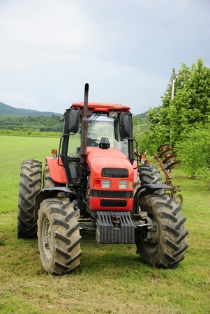 incorporation: Red tractor parked on a grass field  Stock Photo