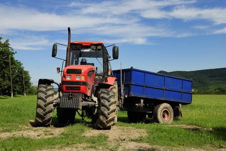 Red tractor with blue trailer on a grass field photo