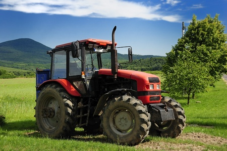 Red tractor with blue trailer on a grass field Stock Photo - 9015151