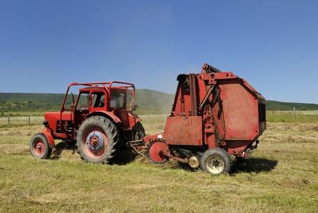 baler: Circular hay baler and red tractor