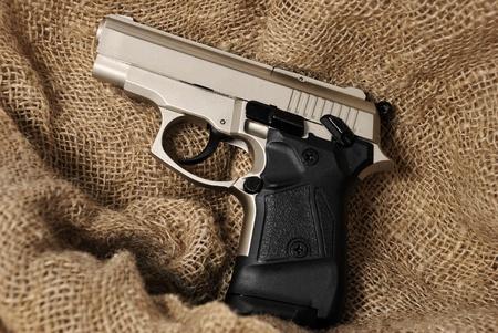 Silver handgun on burlap background photo