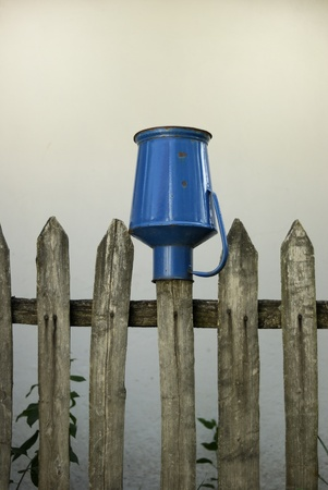 Milk jug on a fence photo