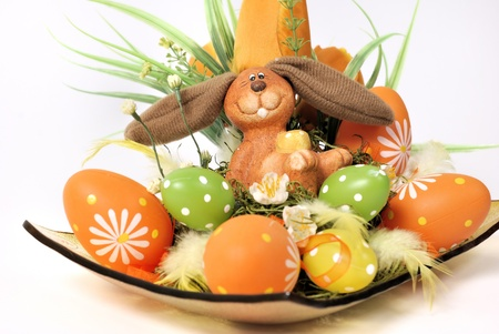 Easter decoration - bunny in a wicker basket with flowers and eggs in green, orange and yellow photo