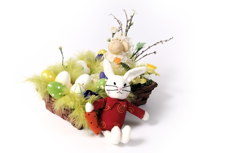 Easter decoration - bunny and a lamb in a wicker basket with flowers and eggs in green, white and yellow photo