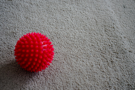 back ache: red massage ball with spikes
