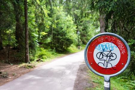 no pase: no pase la señal de pare para bicicletas en el bosque con etiquetas de graffiti Foto de archivo