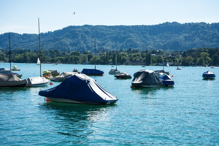 boat on lake zurich in summer with uetliberg in the back