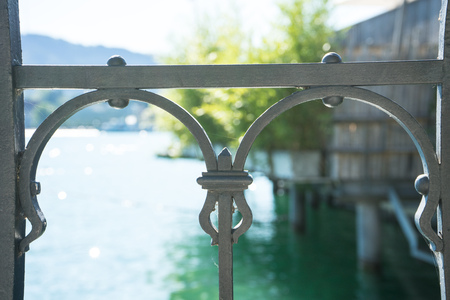lake view through old iron rail with boats