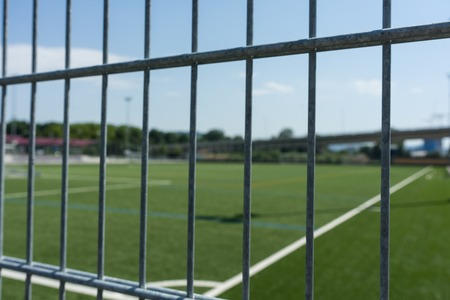 football soccer field viewed through gate Stock Photo