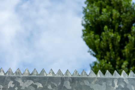 security symbol: Barbed wire fence against the blue cloudy sky Stock Photo