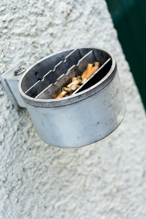 Metal ashtray on a wall full with cigarette old retro style not cleaned