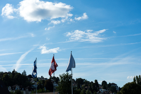 swiss national and zurich canton flag with blue cloudy sky Stock Photo
