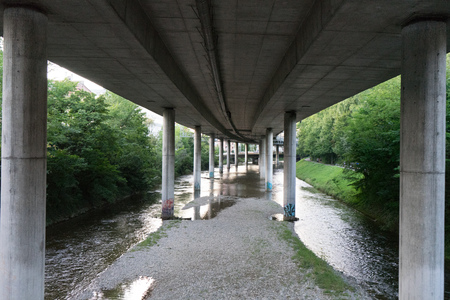 curve road: highway underpass from concrete with small river wide angle Stock Photo