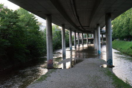 highway underpass from concrete with small river wide angle Stock Photo