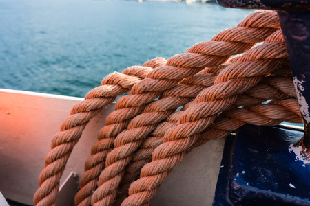 convoluted: Closeup of an old red frayed boat rope, water background with landscape
