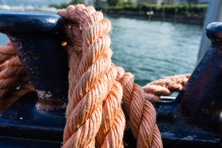 Closeup of an old red frayed boat rope, water background with landscape