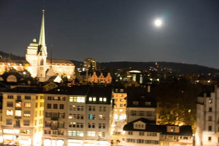 zurich city by night with full moon shinging and light on buildings
