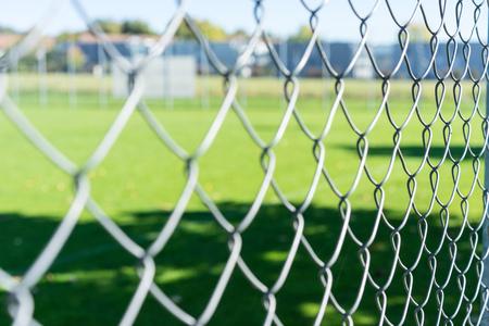 football field seen through iron fence