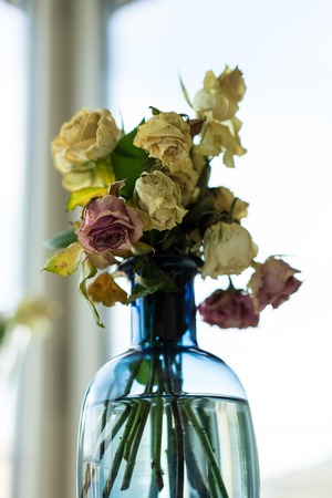 Bouquet of withered roses in glass vase