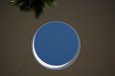 hole in roof ceiling with palm and blue sky Stock Photo