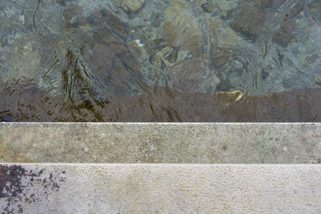 Descend grey concrete stairs into the water, concept photography