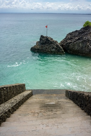 Stair in to the ocean with big rock in water