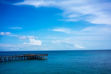 Wood pier and calm ocean water with blue sky and clouds