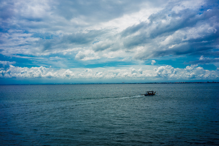 Traditional fisher-boat sailing on water with cloudy sky