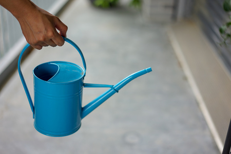 Hand holding blue watering can for urban gardening
