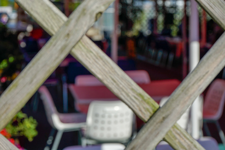 Restaurant chairs and tables seen through fence