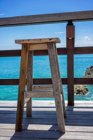 Empty wood chairs with ocean view, holiday mood