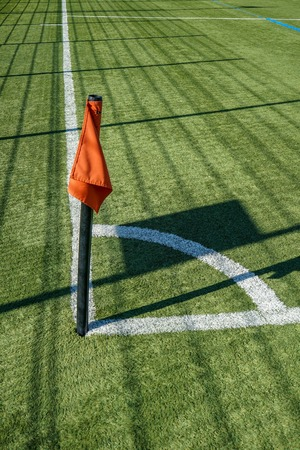 Red corner flag on football or soccer pitch and white lines 写真素材
