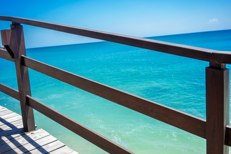 Wood hand rail and ocean horizon with turquoise water